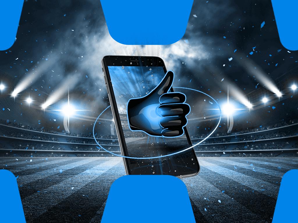 Handy mit Daumen hoch auf Fussballfeld im Hintergrund